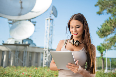 digital wave: Beautiful young woman with vintage music headphones around her neck, surfing internet on a tablet pc and standing against background of satellite dishes that receives wireless signals from satellites.