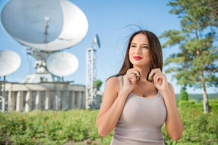 signals: Beautiful young woman wearing vintage music headphones around her neck and standing against background of satellite dish that receives wireless signals from satellites. Stock Photo