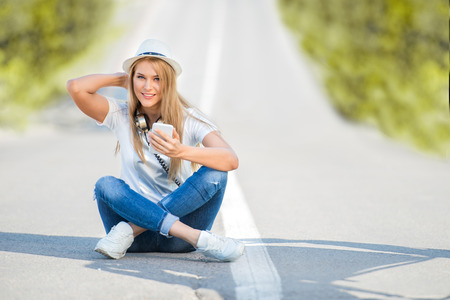 surfing the internet: Happy young woman with vintage music headphones around her neck, surfing internet on a smartphone and sitting on a separating strip against road background. Stock Photo