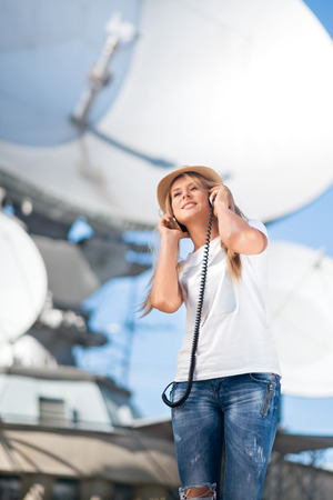 antenna: Happy young woman in hat listening to the music in vintage music headphones and dancing against background of satellite dishes that receive wireless signals from satellites. Stock Photo