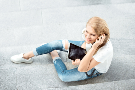surfing the internet: Top view of a happy young woman, listening to the music in vintage music headphones, surfing internet on a tablet pc and sitting on stairs against urban city background.
