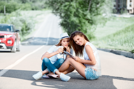 strips away: Happy young women sitting on the road, drinking coffee from a takeaway coffee cup, wearing music headphones, using tablet and buying music online against city background.