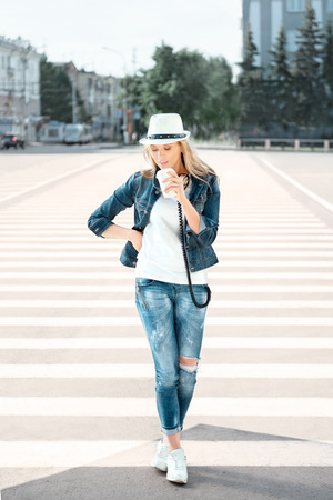 crossing: Beautiful young woman in a hat and jeans jacket with a disposable coffee cup, standing on the road with zebra crossing, drinking coffee, and dancing against urban city background.