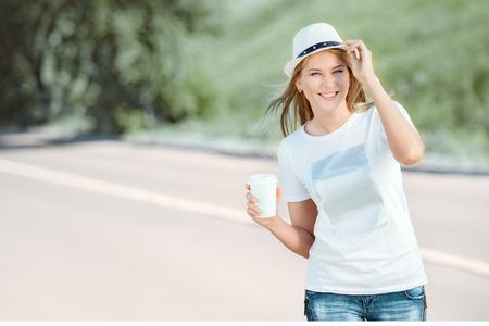 使い捨てのコーヒー カップと歩いて、コーヒーを飲みながら、都市の自然背景に笑みを浮かべて美しい若い女性。 写真素材