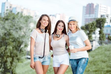 Trois heureux jeunes femmes avec un casque de musique vintage et une tasse de café à emporter, debout sur le fond de la ville urbaine et souriant.
