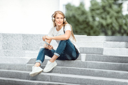 Happy young woman with vintage music headphones and a take away coffee cup, surfing internet on tablet pc, listening to the music and sitting on stairs against urban city background. Foto de archivo