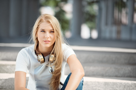 lovers: Beautiful young woman with vintage music headphones around her neck, sitting against urban city background and looking straight. Stock Photo