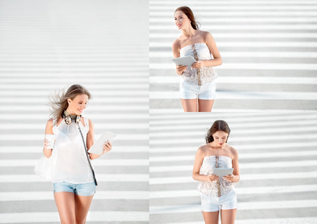 woman shop: Photoset of a happy young woman standing on the road with zebra crossing, drinking coffee from a takeaway coffee cup, wearing music headphones and buying music on tablet online against road background.