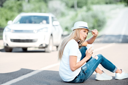 strips away: Happy young woman with music headphones around her neck, drinking coffee from a takeaway coffee cup and sitting on a separating strip against road background.