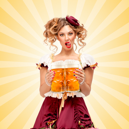 Beautiful sexy Oktoberfest waitress, wearing a traditional Bavarian dress dirndl, serving two big beer mugs in a tavern and licking her lips on colorful abstract cartoon style background.