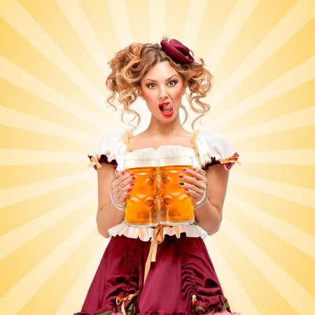Belle serveuse Oktoberfest sexy, vêtue d'une robe bavaroise traditionnelle dirndl, desservant deux grandes tasses de bière dans une taverne et léchant ses lèvres sur coloré abstrait de style de bande dessinée. Banque d'images - 44904414