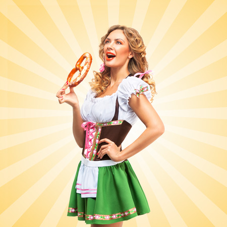 nude girl young: Beautiful sexy Oktoberfest woman wearing a traditional Bavarian dress dirndl with open mouth eating a pretzel on colorful abstract cartoon style background.