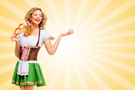 girl happy: Beautiful sexy Oktoberfest woman wearing a traditional Bavarian dress dirndl posing with a soft salty pretzel on colorful abstract cartoon style background.
