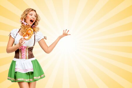 sexy costume: Sexy Oktoberfest woman wearing a traditional Bavarian dress dirndl with a pretzel in hands on colorful abstract cartoon style background. Stock Photo