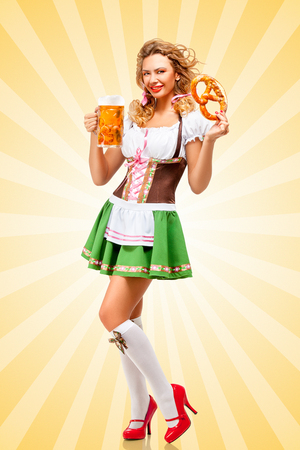 Beautiful sexy Oktoberfest woman wearing a traditional Bavarian dress dirndl holding a pretzel and beer mug in hands on colorful abstract cartoon style background. Stock Photo