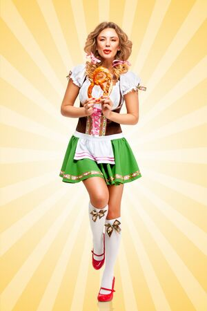 girl young: Beautiful happy dancing Oktoberfest woman wearing a traditional Bavarian dress dirndl holding a pretzel in hands on colorful abstract cartoon style background. Stock Photo