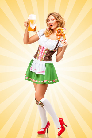 clothes cartoon: Beautiful sexy Oktoberfest woman wearing a traditional Bavarian dress dirndl holding a pretzel and beer mug in hands on colorful abstract cartoon style background. Stock Photo