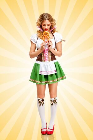 emotional: Beautiful sad sexy Oktoberfest woman wearing a traditional Bavarian dress dirndl holding a pretzel in hands on colorful abstract cartoon style background.