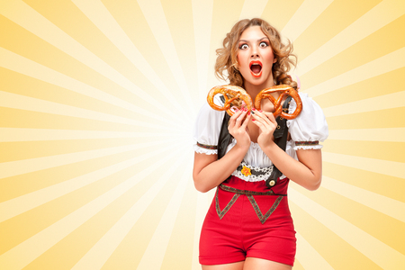 sexy blonde girl: Beautiful sexy woman wearing red jumper shorts with suspenders in a form of a traditional dirndl, holding with hunger two pretzels on colorful abstract cartoon style background.