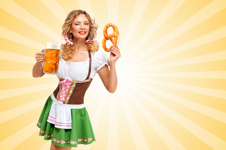 Beautiful sexy Oktoberfest woman wearing a traditional Bavarian dress dirndl holding a pretzel and beer mug in hands on colorful abstract cartoon style background. Фото со стока