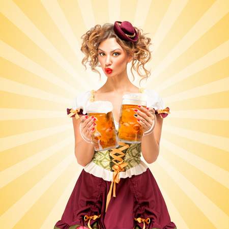 beer party: Beautiful sexy Oktoberfest waitress, wearing a traditional Bavarian dress dirndl, serving two big beer mugs in a tavern and licking her lips on colorful abstract cartoon style background.