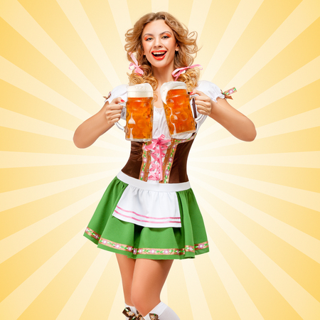 Beautiful sexy Oktoberfest woman wearing a traditional Bavarian dress dirndl serving two beer mugs with happy smile on colorful abstract cartoon style background. Stock Photo