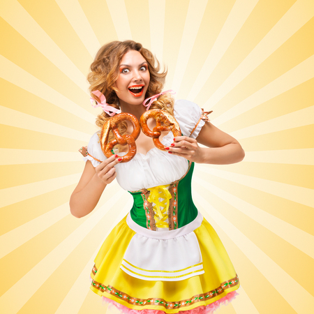 sexy girl: Happy excited sexy Oktoberfest woman wearing a traditional Bavarian dress dirndl holding two pretzels on colorful abstract cartoon style background.