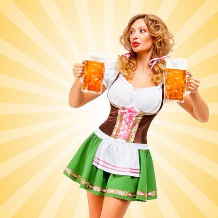 oktoberfest background: Beautiful sexy Oktoberfest woman wearing a traditional Bavarian dress dirndl looking aside with two beer mugs on colorful abstract cartoon style background.