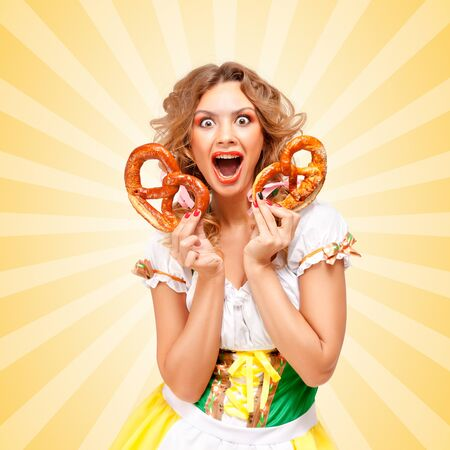 sexy costume: Beautiful happily excited sexy Oktoberfest woman wearing a traditional Bavarian dress dirndl holding two pretzels on colorful abstract cartoon style background. Stock Photo