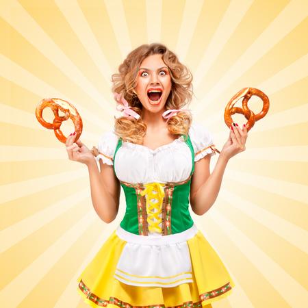 jolie fille: Belle femme sexy indign�e Oktoberfest portez un traditionnel dirndl robe bavaroises tenant deux bretzels, montrant grimace agressive sur color� abstrait de style de bande dessin�e. Banque d'images