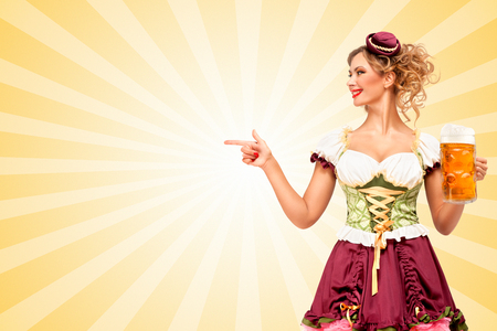 girl glasses: Beautiful smiling sexy Oktoberfest waitress wearing a traditional Bavarian dress dirndl holding beer mug, and pointing aside on colorful abstract cartoon style background. Stock Photo