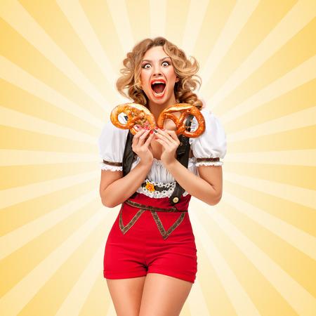persona feliz: Hermosa mujer conmocionados Oktoberfest sexy vistiendo pantalones cortos de jersey rojo con tirantes en forma de un dirndl tradicional, la celebración de dos pretzels en fondo colorido del extracto del estilo de dibujos animados. Foto de archivo
