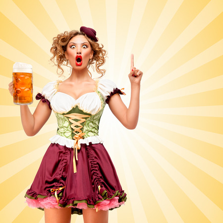 woman open mouth: Beautiful smiling sexy Oktoberfest waitress wearing a traditional Bavarian dress dirndl holding a beer mug, and coming up with plan on colorful abstract cartoon style background. Stock Photo