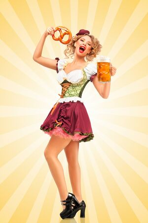 clothes cartoon: Beautiful excited Oktoberfest waitress wearing a traditional Bavarian dress dirndl holding a pretzel and beer mug, and making grimaces on colorful abstract cartoon style background. Stock Photo