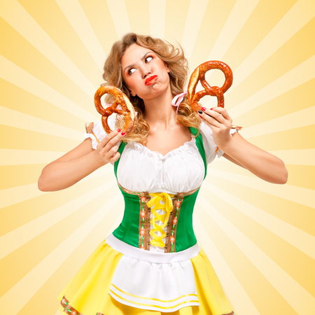 grimace: Beautiful sexy offended Oktoberfest woman wearing a traditional Bavarian dress dirndl holding two pretzels, puffing her cheeks and pouting on colorful abstract cartoon style background.
