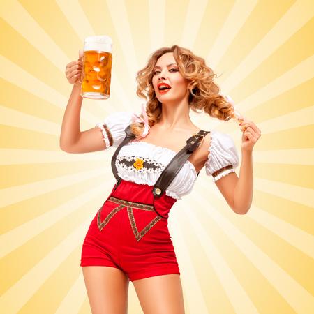 mujeres eroticas: Hermosa coquetear mujer sexy con pantalones cortos de color rojo puente con tirantes como dirndl tradicional, sosteniendo una jarra de cerveza en el fondo colorido del extracto del estilo de dibujos animados. Foto de archivo