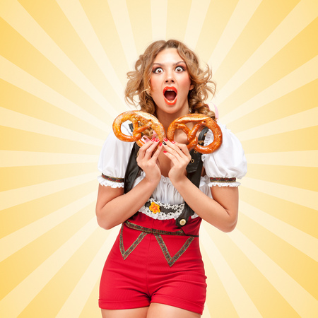 Beautiful shocked sexy Oktoberfest woman wearing red jumper shorts with suspenders in a form of a traditional dirndl, holding two pretzels on colorful abstract cartoon style background.