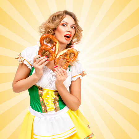 sexy costume: Beautiful sexy shocked Oktoberfest woman wearing a traditional Bavarian dress dirndl holding two pretzels and feeling scared on colorful abstract cartoon style background. Stock Photo