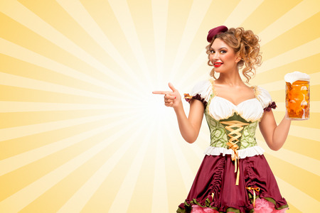 aside: Beautiful smiling sexy Oktoberfest waitress wearing a traditional Bavarian dress dirndl holding beer mug, and pointing aside on colorful abstract cartoon style background. Stock Photo