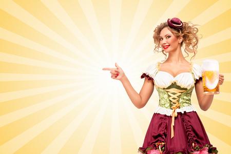 Mooi glimlachend sexy Oktoberfest serveerster gekleed in een traditionele dirndl Beierse kleding met bier mok, en wijst opzij op kleurrijke abstracte cartoon stijl achtergrond.