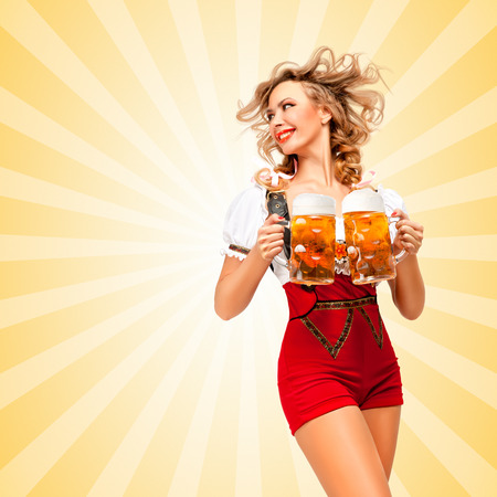 tempting: Beautiful tempting sexy woman wearing red jumper shorts with suspenders as traditional dirndl, serving two beer mugs and looking aside on colorful abstract cartoon style background. Stock Photo