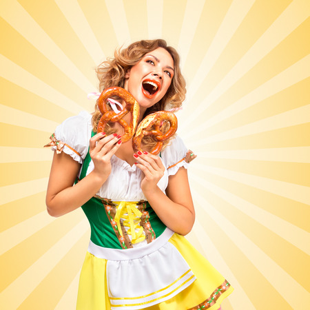 sexy food: Beautiful happily excited sexy Oktoberfest woman wearing a traditional Bavarian dress dirndl holding two pretzels with joy on colorful abstract cartoon style background. Stock Photo