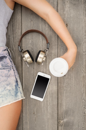 hold on: Beautiful young woman lying on the wooden floor with music headphones, smartphone and a take away coffee cup; view from above.