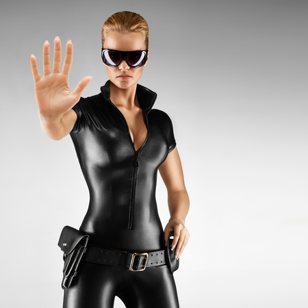 sex pose: Female security guard in tight, black, sexy outfit with pistol.