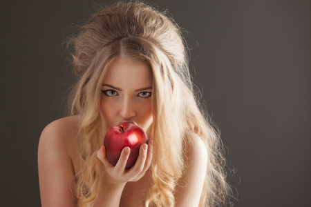 beautiful naked woman: Portrait of a sexy beautiful nude pin-up girl from 60s or 70s, eating and biting a fresh red apple with temptation on dark background. Stock Photo