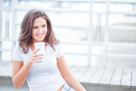 tomando café: Hermosa mujer joven sosteniendo una toma de distancia taza de café y se sienta en el puente contra el fondo del agua.