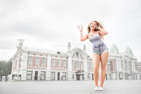 donna che balla: Felice giovane donna con le cuffie di musica, in possesso di un take away tazza di caffè, l'ascolto della musica e la danza contro lo sfondo della città.