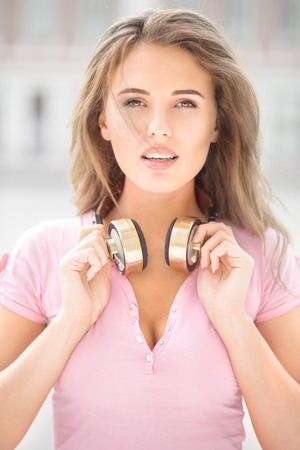 pretty face: Beautiful young woman with vintage music headphones on her neck, standing against urban city background and listening to the music.