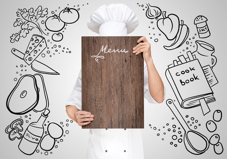 main board: Restaurant chef on a sketchy background hiding behind a wooden chopping board for a business lunch menu with prices. Stock Photo
