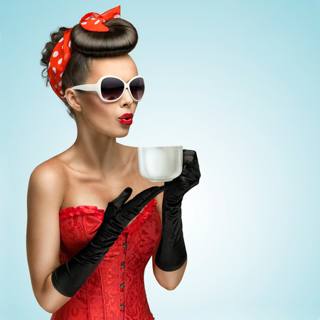 tastes: Three-quarter portrait of glamourous pinup girl wearing vintage gloves and red ribbon in her hair, holding a cup of hot coffee or tea and cooling it.